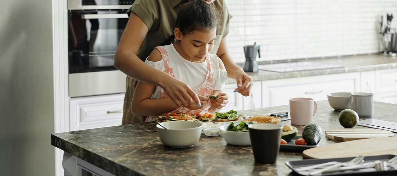 Niña y madre en la cocina para una gastronomía sostenible