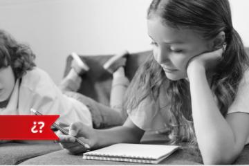 dos niños en un sofa escribiendo en una libreta