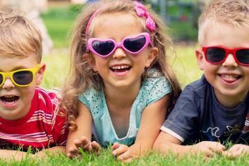 tres niños con divertidas gafas de sol y riendo para feliz verano