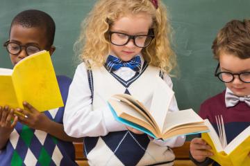 tres nens llegint llibres atentament per a propostes didàctiques