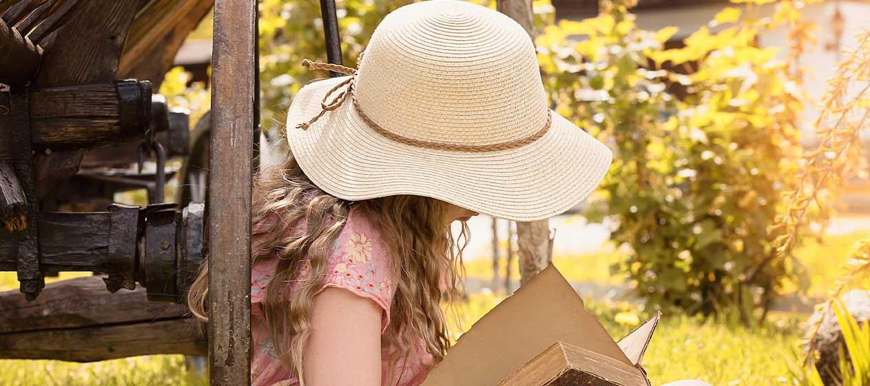 niña leyendo apoyada en un árbol para un verano diferente