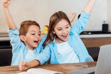 niños divirtiéndose mirando un ordenador para gamificación online