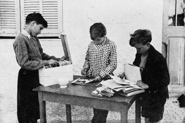 Foto histórica de un grupo de niños en los 50 usando la imprenta de Célestin Freinet