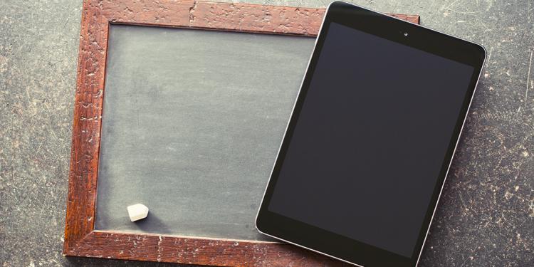 imagen de pizarra y tiza con tablet encima para retos que debe afrontar la educación hoy