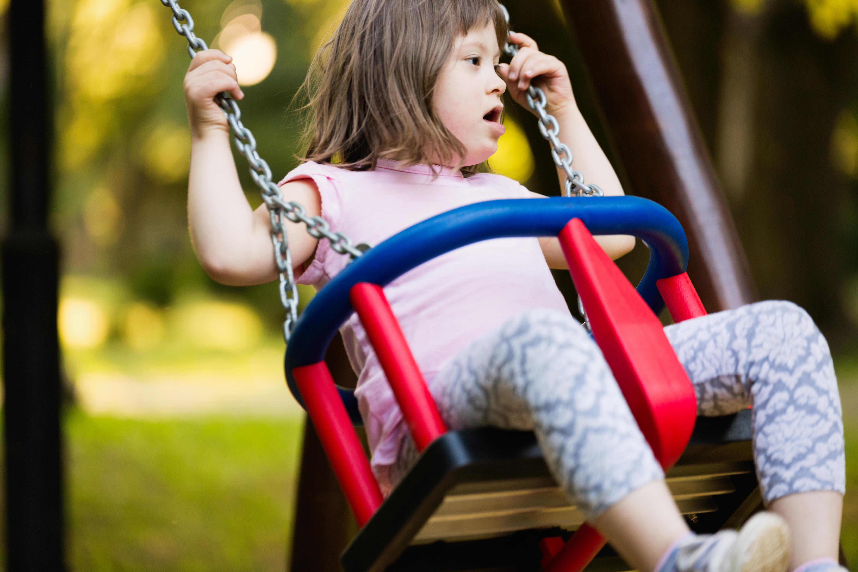 Niña con síndrome de Down en los columpios