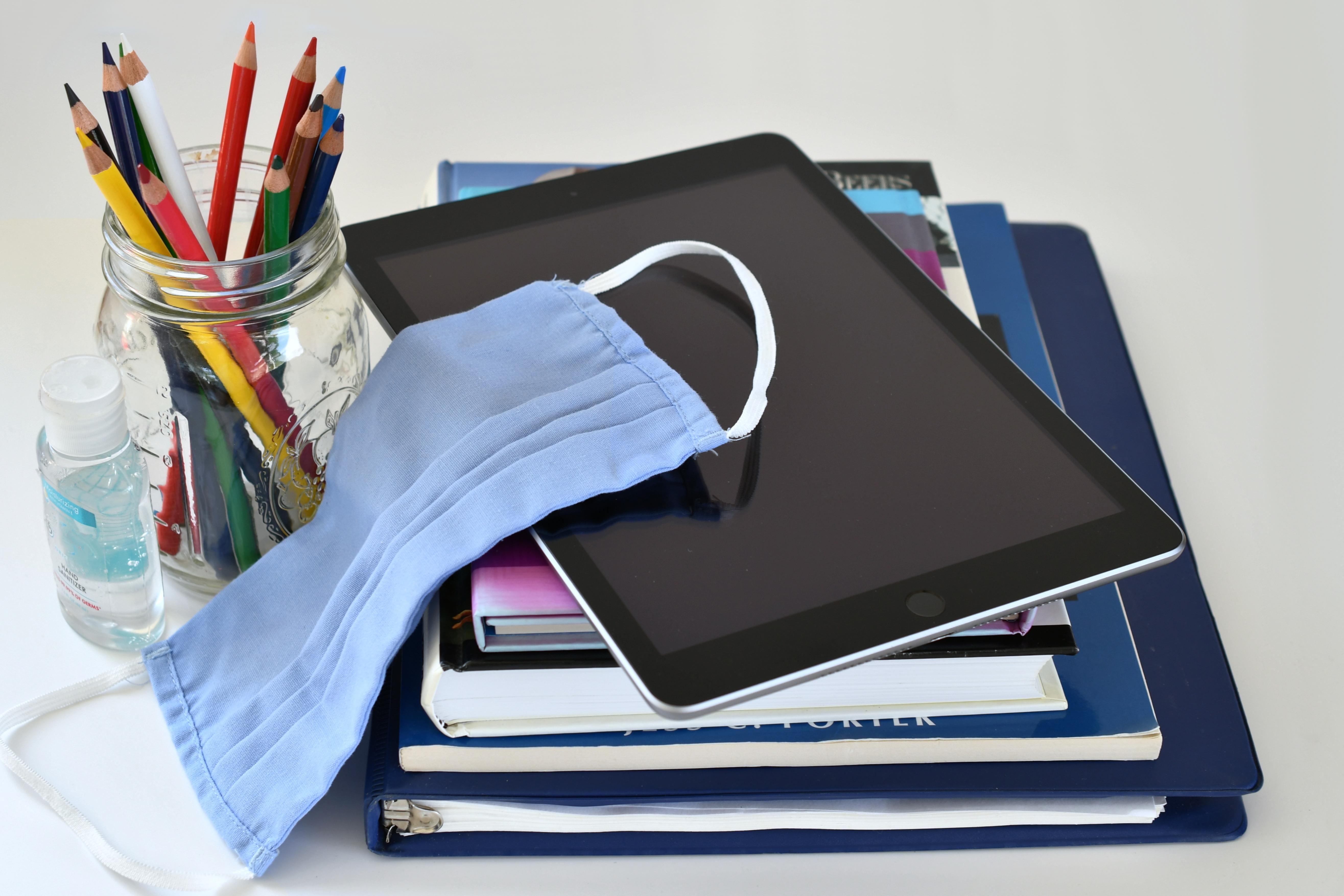 Tablet, mascarilla y libros para ilustrar la transición a la LOMLOE