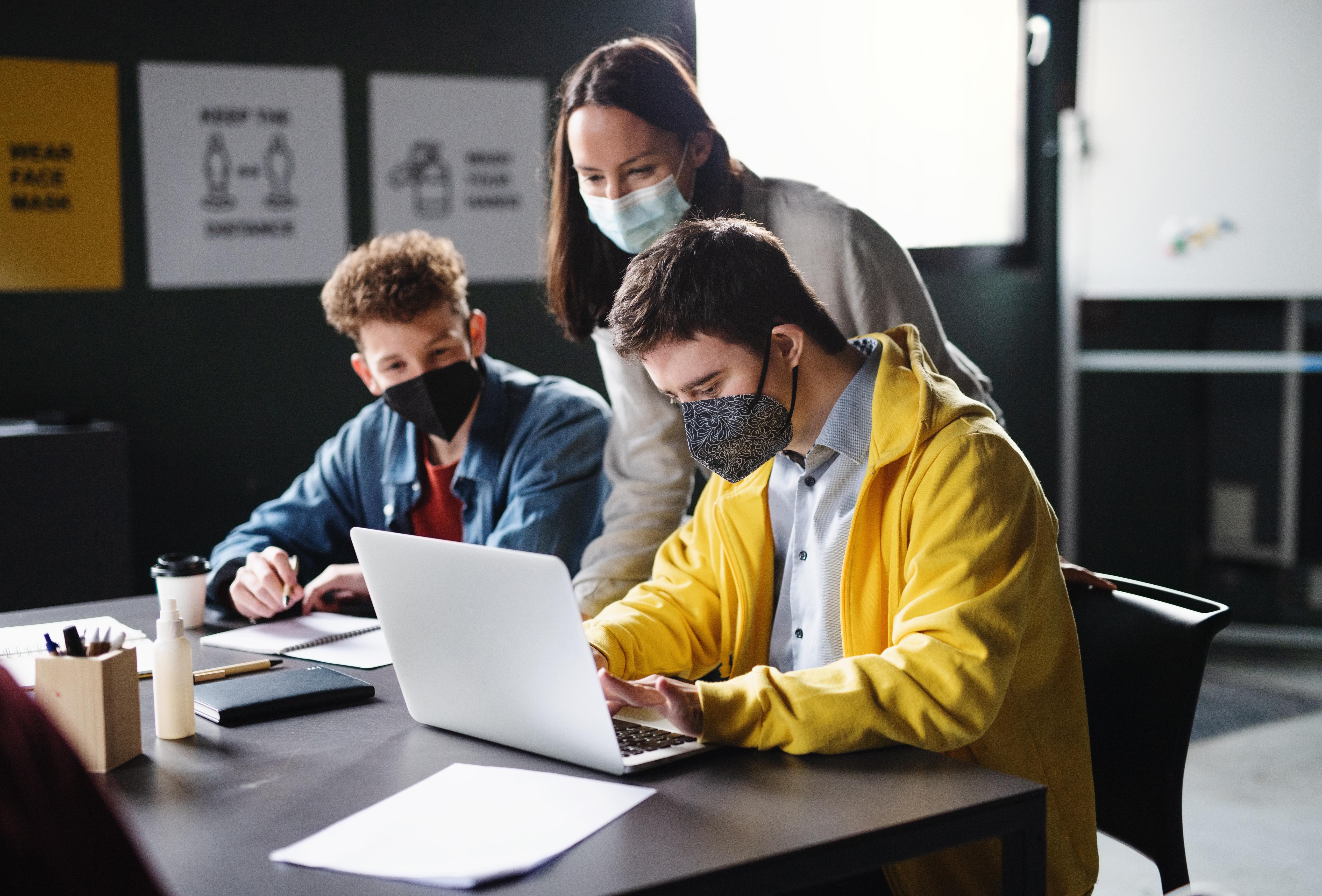 Grup a classe amb mascareta, i amb educació híbrida paper i digital