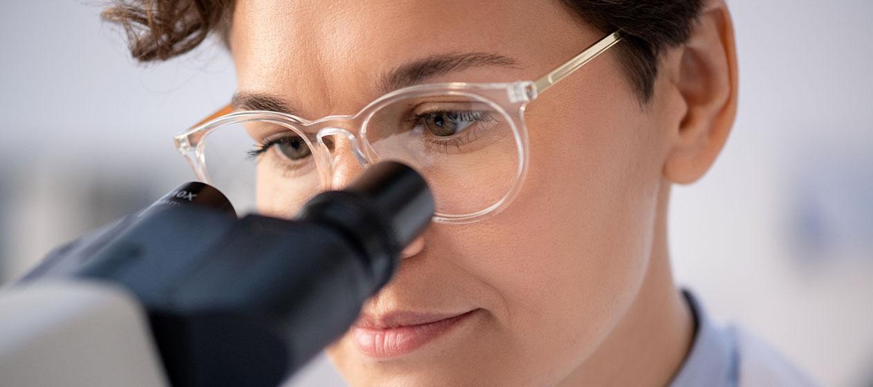 Mujer mirando a través de microscopio para ilustrar las mujeres científicas