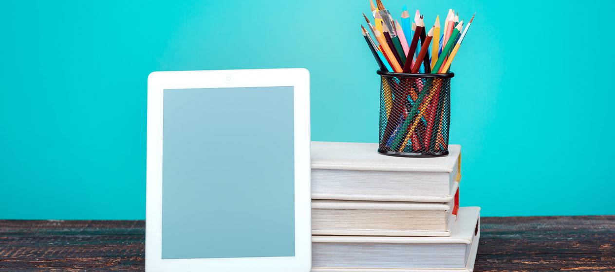 Libros, lápices y tablet para ilustrar la preparación a la nueva LOMLOE
