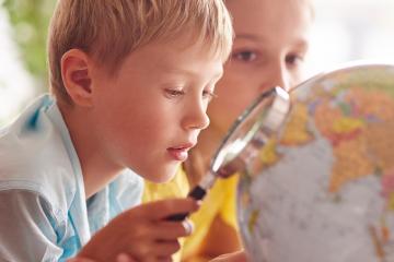 niños mirando bola del mundo con lupa para ABP: criterios