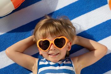niño tumbado con gafas de sol divertidas para feliz verano