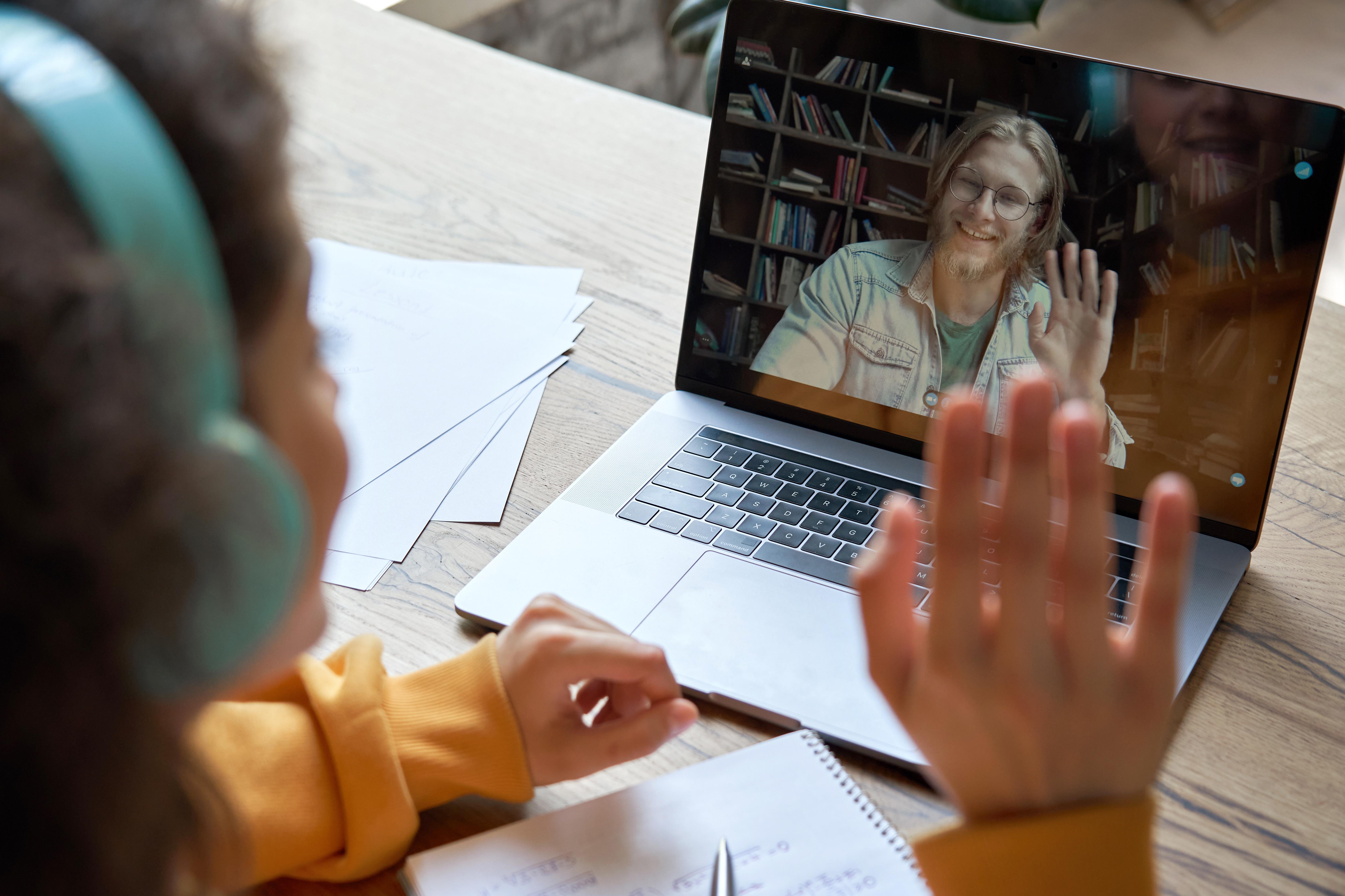 niña y profesor se saludan por pantalla