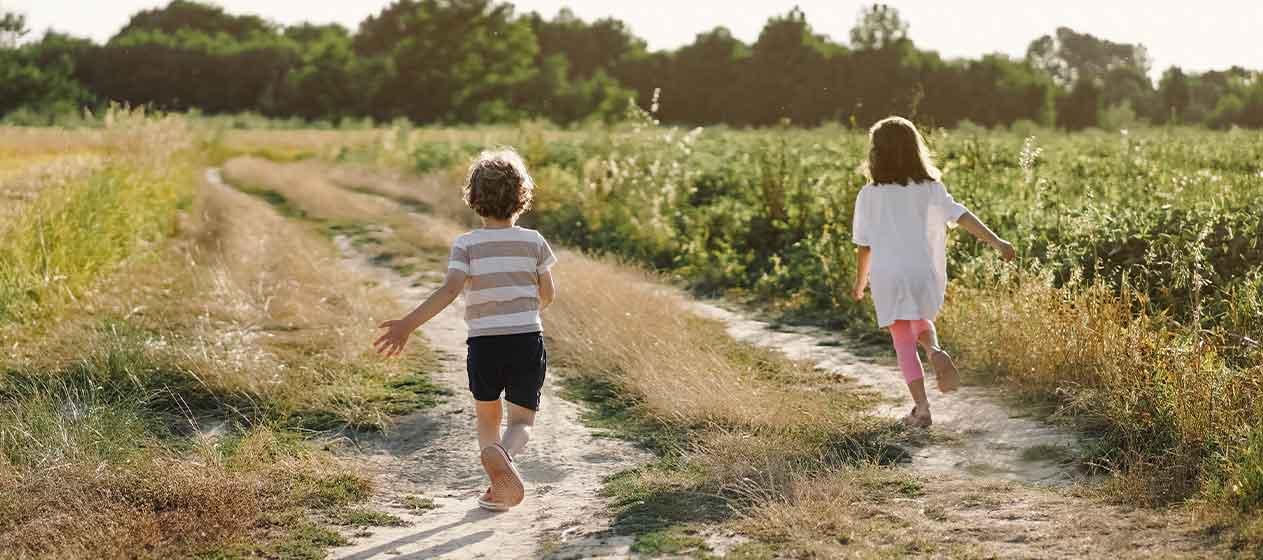 Niños corriendo en verano para ilustrar la importancia del contacto con la naturaleza