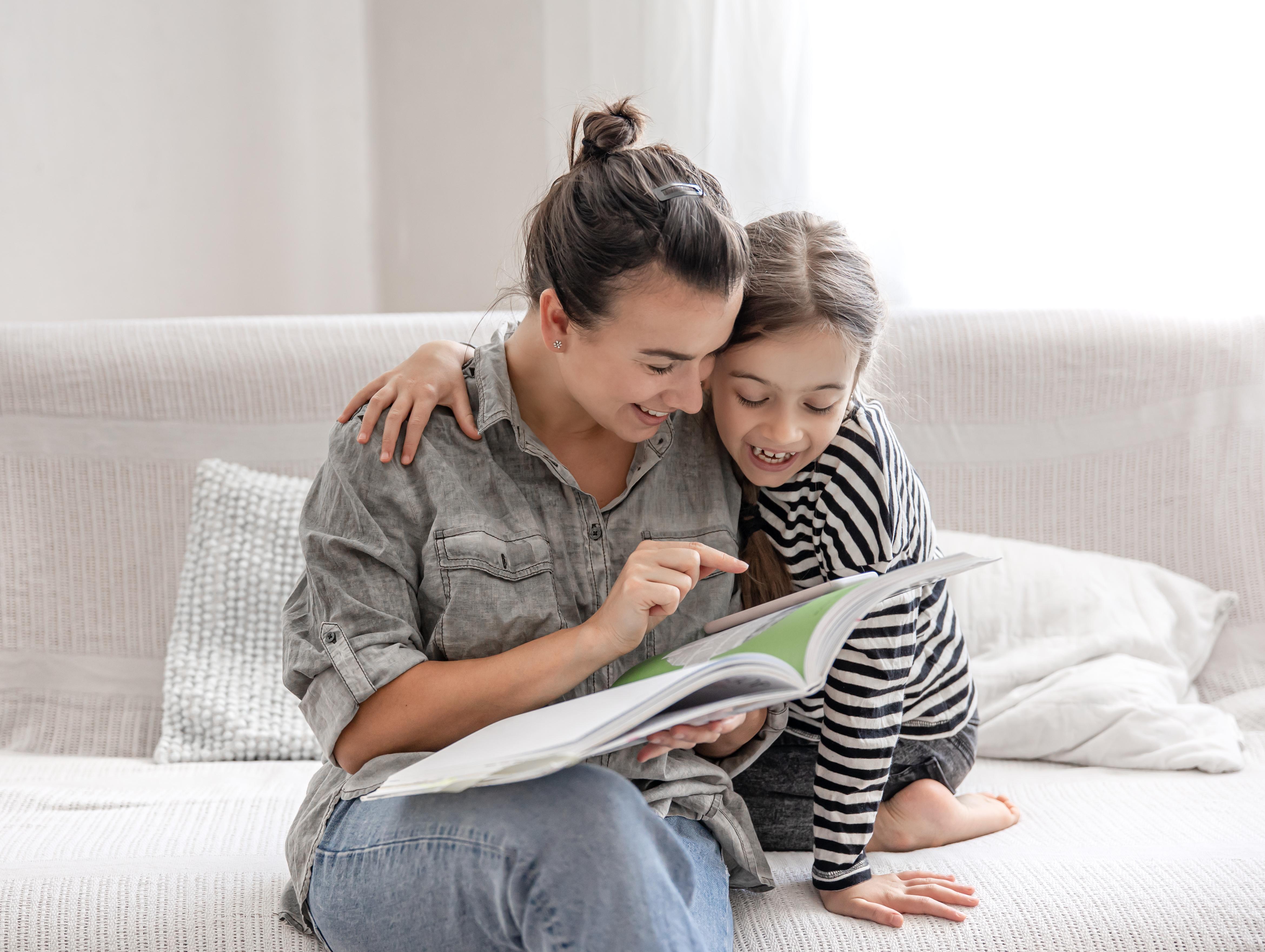Mare i filla a casa amb un llibre per il·lustrar repassar a les vacances