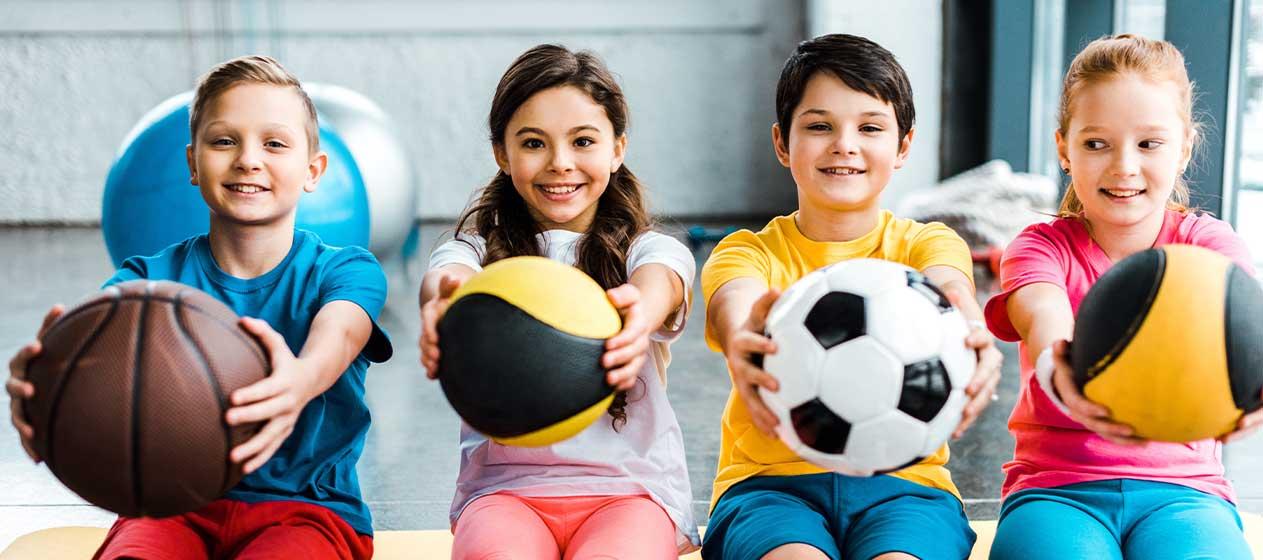 Niños con pelota de distintas disciplinas para ilustrar la importancia del deporte