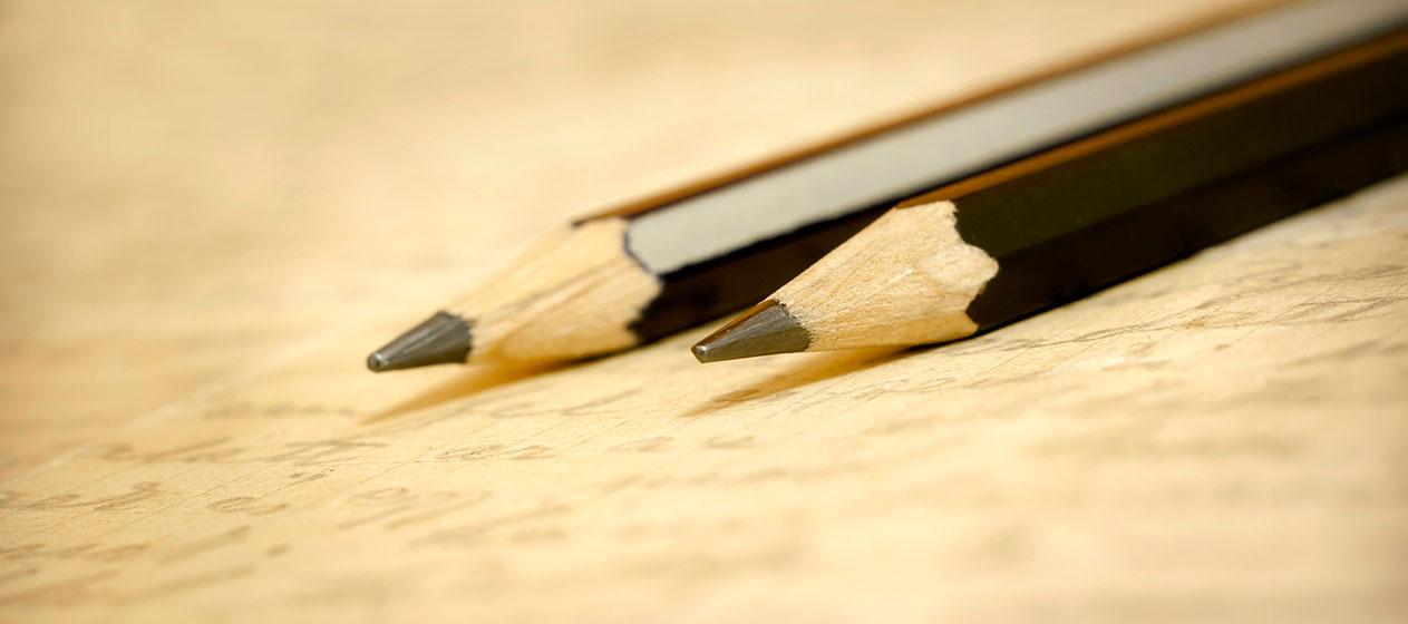 Dos lápices sobre una hoja ilustrando la evaluación en la LOMLOE