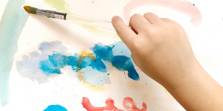 Mano de niño dibujando con pintura de colores